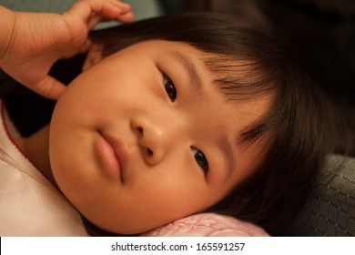 Pretty toddler asian girl laying down and watching tv