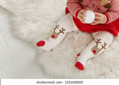 Pretty Toddler Girl in a Christmas Dress. Lovely red and white girly pantyhose with Rudolf. Baby outfit for winter holidays