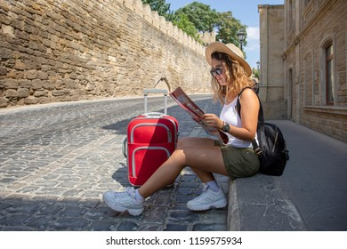 Pretty tourist girl sitting on the roadside in the old town and is looking at the map. Travler girl with suitcase. Tourist concept.