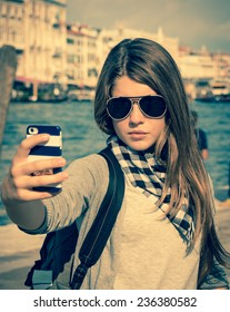 Pretty tourist girl in sunglasses taking self portrait with the Grand Canal in the background. Venice. Italy