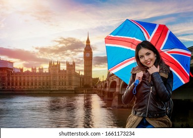 A pretty tourist woman with an umbrella with British Flag on it stands in front of the Big Ben during a sightseeing trip through London