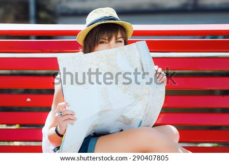 Pretty tourist young woman sitting on red bench and hiding on the map of  Europe. f8dc71e69e64