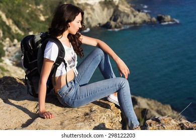 Pretty traveler girl is sitting on rock edge over sea background  with backpack, summer time