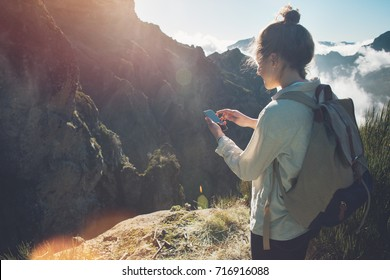 Pretty traveling woman standing on top of  mountain at sunset and using mobile phone.