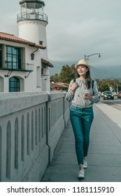 a pretty travle woman walking down the sidewalk and holding a smartphone happily in the town.