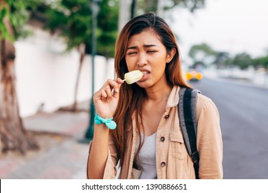 Pretty unhappy Asian woman having teeth problem while eating ice-cream on street