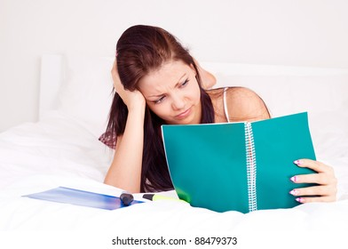 pretty unhappy girl sitting on the bed at home and doing homework