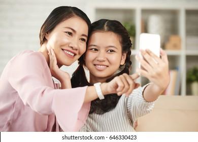 Pretty Vietnamese teenage girl taking selfie with her mother