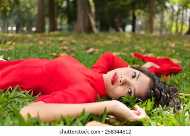 Pretty Vietnamese woman relaxing on the grass lying on her back in a traditional red dress with her arms outstretched looking at the camera