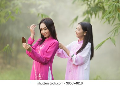 Pretty Vietnamese woman wearing a traditional at bamboo garden