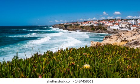 Pretty view of Praia das Maçãs from the cliffs with yellow flowers in the foreground & the village & waves in the background. Taken on a sunny day in summer.