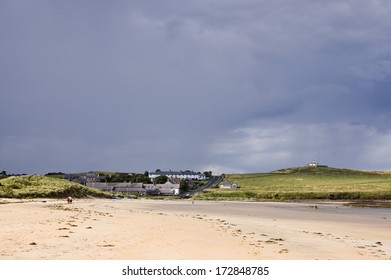 The pretty village of Low Newton by the Sea in Northumberland with heavy rainclouds gathering