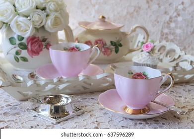 Pretty Vintage Pink Roses Afternoon Tea Party - teacup, saucer, teapot and silver cutlery flatware, tea strainer on a wooden tray and lace table cloth
