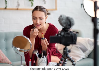 Pretty vlogger influencer filming a beauty video podcast, live streaming to online audience