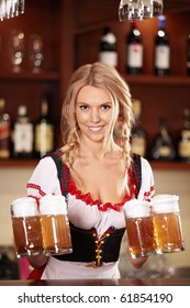 A pretty waitress with beers at the bar