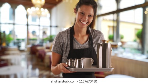 Pretty waitress in restaurant carrying tray with coffee beverages