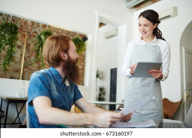 Pretty waitress taking order of one of guests