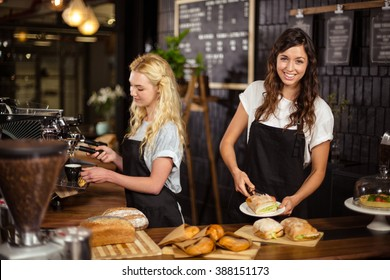 Pretty waitresses behind the counter working at the coffee shop