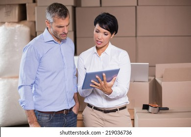Pretty warehouse manager using tablet pc with colleague in a large warehouse