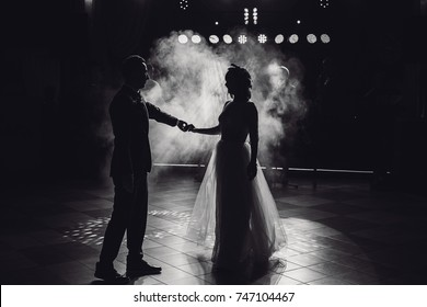 Pretty wedding couple dances in the smoke and looks misterious