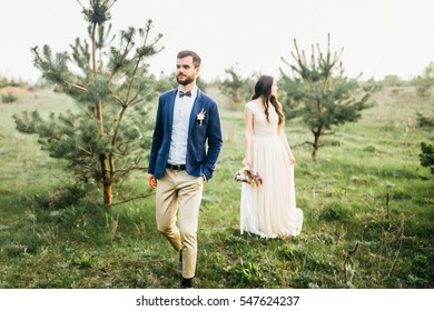 Pretty wedding couple walking on the glade