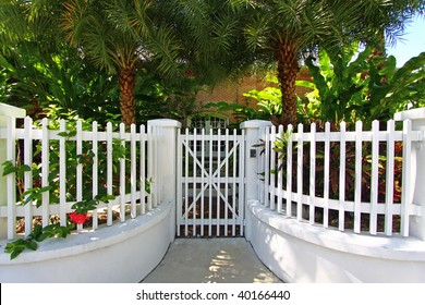 Pretty white gate and fence surrounded by lush tropical foliage.