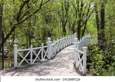 Pretty white wooden pedestrian bridge over stream in Domaine Maizerets public park during sunny spring afternoon, Quebec City, Quebec, Canada