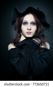 Pretty witch in hat posing over dark background
