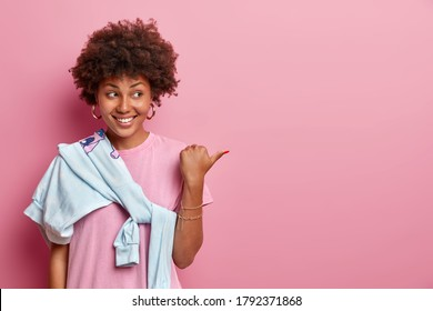 Pretty woman with Afro hair helps to pick best choice, points thumb aside on copy space, advertises product, smiles happily, wears rosy t shirt and sweater tied over shoulder. Your promo here