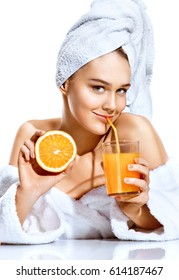 Pretty woman after bath in white bathrobe and towel on her head. Portrait of smiling woman holding orange juice and orange fruit. Happy and healthy