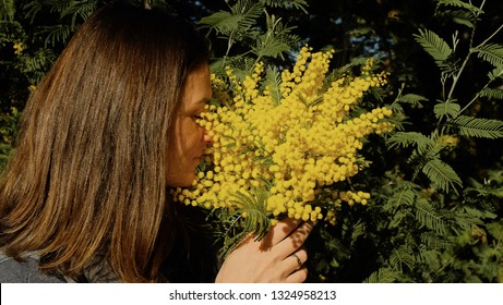 Pretty woman against mimosa tree with flowers on blue sky and sunny day