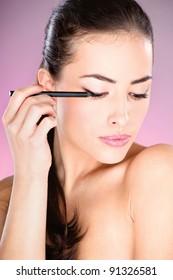 pretty woman applying cosmetic pencil on eye