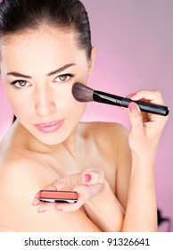pretty woman applying cosmetic powder brush