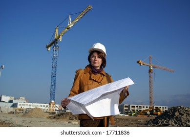 Pretty woman architect holding blueprints and standing in the building site