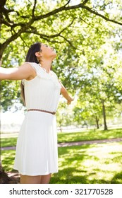 Pretty woman with arms outstretched while standing in park
