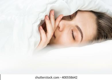 Pretty woman asleep under white blanket. Closed eyes. Sweet Dreams. Sleeping Beauty portrait. Relaxed time
