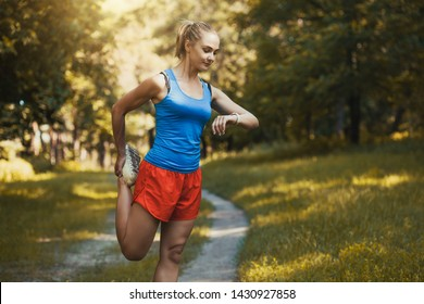 Pretty woman athlete doing exercises before jogging through the summer forest