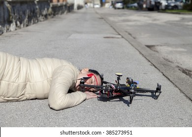 Pretty woman attacked by drone quadrocopter with bleeding head injuries,  lying on sidewalk in the city, space for text