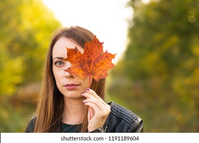 Pretty woman with autumn yellow maple leaves on forest background