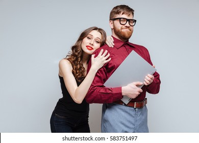 Pretty Woman from back of Male nerd in eyeglasses which holding laptop. Isolated gray background