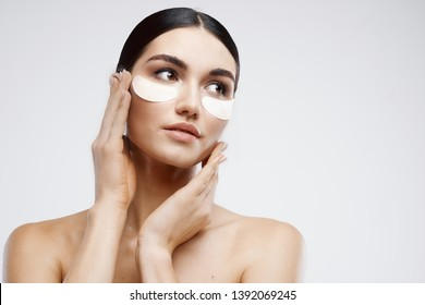 Pretty woman with bare shoulders collagen on face gray background skin care spa procedure