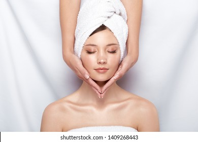 pretty woman in bath towel on her head receiving facial massage, beauty theraphy after bath, spa treatment for females