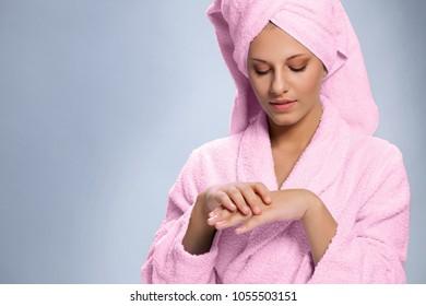 Pretty woman in bathrobe moisturizing hands with cream