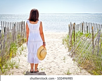 Pretty woman at the beach with a straw hat