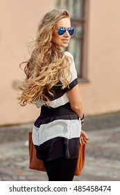 Pretty woman with beautiful curly blond hair outdoor portrait