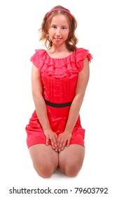 Pretty woman in beautiful red dress is sitting on isolated white background.