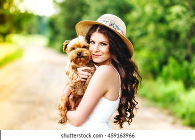 pretty woman beautiful young happy with long dark hair in white dress holding small dog puppy