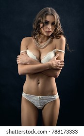 pretty woman with big breast in white lingerie on dark background undressing