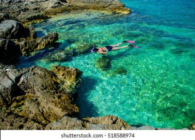 Pretty Woman in Bikini Snorkeling through Turquoise Water at the Coast