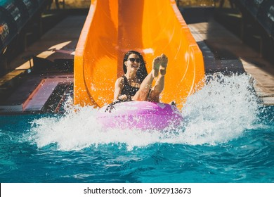 pretty woman in black bikini with legs up coming down on the inflatable ring by the slide in the aqua park. Summer Vacation. Enjoying suntan. Weekend on resort